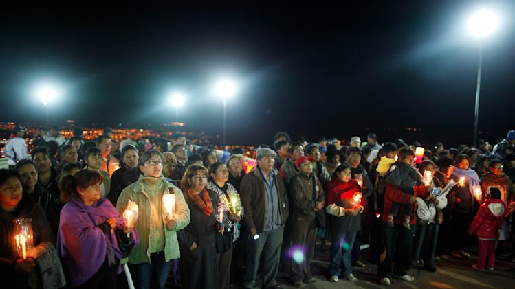 """Pilgrims holding candles pray at the base of the statue of the Virgin Mary on Santa Barbara hill before sunrise in the mining city of Oruro, Bolivia, Friday, Feb. 1, 2013. The statue, known in Spanish as """"Virgen del Socavón,"""" or the Virgin of the Tunnel, is Oruro's patron, venerated in particular by miners and folkloric Carnival dancers. The statue was unveiled on Friday to mark the start of Carnival in Oruro, which coincides with celebrations honoring the Virgin that starts on Saturday, Bolivia's largest religious event. (AP Photo/Juan Karita)"""