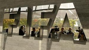 Journalists are reflected in a logo at the FIFA headquarters in Zurich