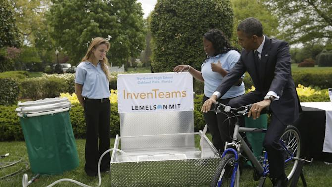 President Barack Obama pedals  bicycle-powered emergency water-sanitation station for Payton Karr, 16, left, and Kiona Elliott, 18, center, both from Oakland Park, Fla., to help demonstrate their invention, Monday, April 22, 2103, in the East Garden of the White House in Washington, where the president hosted the White House Science Fair to celebrate the student winners of a broad range of science, technology, engineering and math (STEM) competitions from across the country. The bicycle filters E. Coli and other harmful pathogens from contaminated water. (AP Photo/Pablo Martinez Monsivais)