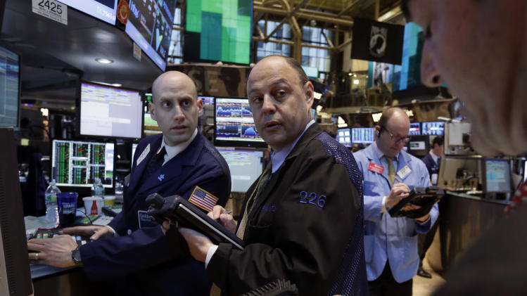 Specialist Meric Greenbaum, left, works with traders on the floor of the New York Stock Exchange Monday, April 29, 2013.  A pair of encouraging economic reports helped propel the stock market up in early trading on Monday. (AP Photo/Richard Drew)