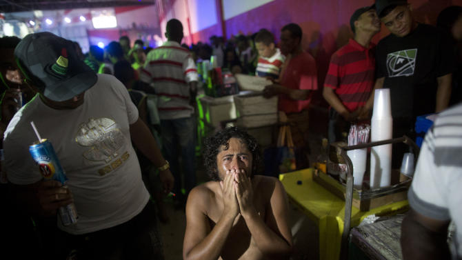 "In this Dec. 8, 2012 photo, a man reacts as he kneels on the floor during a funk ""baile,"" or party, in a slum in western Rio de Janeiro, Brazil. A 2007 law that had made it virtually impossible to hold the traditional open-air funk parties in favelas was repealed in 2009, and the musical genre was recognized as a ""cultural movement."" (AP Photo/Felipe Dana)"