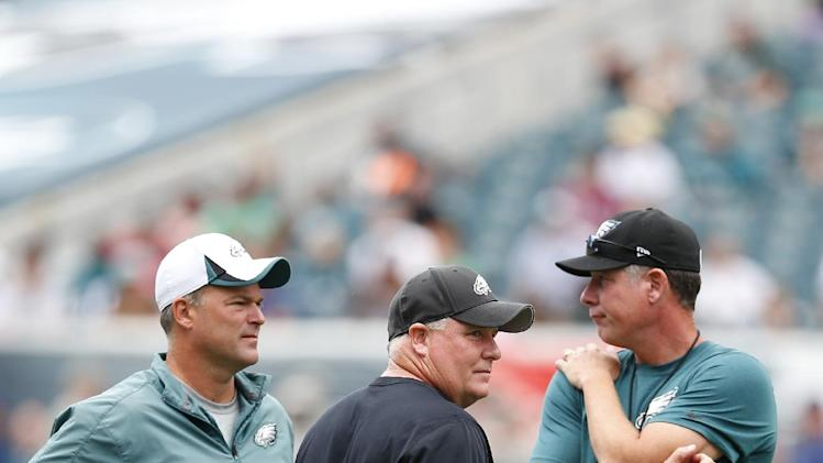 Philadelphia Eagles head coach Chip Kelly, center, stands with defensive coordinator Bill Davis left, and offensive coordinator Pat Shurmur, during NFL football training camp Monday, July 28, 2014, in Philadelphia