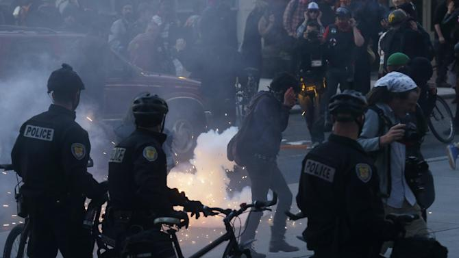 Protesters react as a firework is set off during May Day protests, Wednesday, May 1, 2013, in downtown Seattle. (AP Photo/Ted S. Warren)