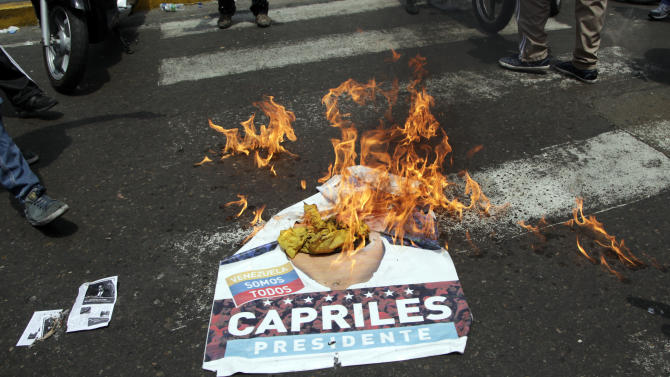 """Government """"Chavista"""" supporters burn an election poster of opposition presidential candidate Henrique Capriles in Los Teques, on the outskirts of Caracas, Venezuela, Tuesday, April 16, 2013.  President-elect Nicolas Maduro is blaming Capriles for seven deaths that the government says occurred in post-election unrest. The government has provided names of some people it says have been killed by opposition activists but has provided no evidence. Capriles is demanding a vote-by-vote recount of Sunday's presidential election. (AP Photo/Ariana Cubillos)"""