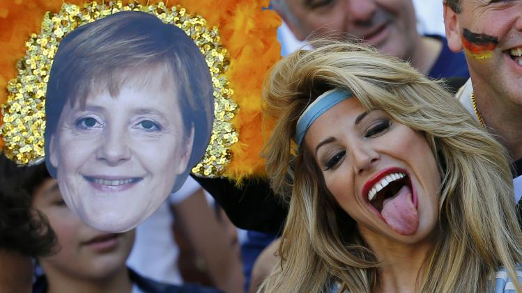An Argentina fan reacts near a mask of German Chancellor Merkel before the team's 2014 World Cup final against Germany in Rio de Janeiro
