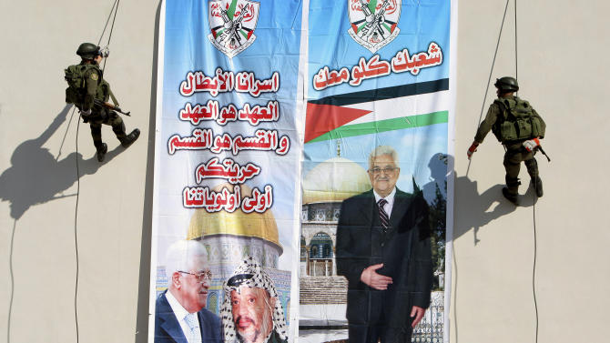"Plestinian security officers slide down from a building next to a banner of President Mahmoud Abbas with Yasser Arafat, in the West Bank town of Jenin, Wednesday, Nov. 28, 2012. The Palestinians will request the UN to upgrade their status to an observer state on November 29. The status could add weight to Palestinian claims for a state in the West Bank, Gaza Strip and east Jerusalem, territories captured by Israel in the 1967 Mideast war from Jordan. Arabic on the left reads ""our hero prisoners, the covenant is the covenant and the section is the section, your liberty will stay our first priority,"" and right, ""all your people (are) with you.""(AP Photo/Mohammed Ballas)"