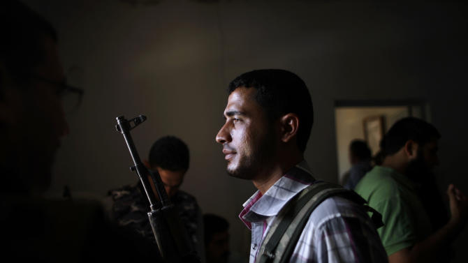A Syrian rebel fighter holds his rifle as he and other fighters head to Aleppo to fight government forces, at their headquarters in Suran, on the outskirts of Aleppo, Syria, Monday, Sept. 10, 2012. (AP Photo/Muhammed Muheisen)
