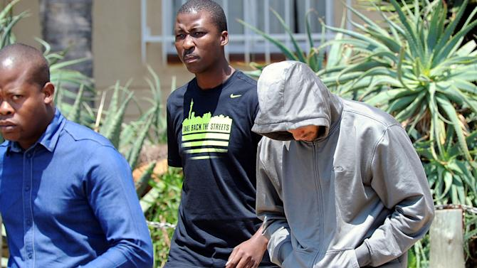 Olympic athlete Oscar Pistorius leaves the Boschkop police station, east of Pretoria, South Africa, Thursday, Feb. 14, 2013 en route to appear in court charged with murder.  Olympic athlete Oscar Pistorius was taken into custody and was expected to appear in court Thursday, after a 30-year-old woman who was believed to be his girlfriend was shot dead at his home in South Africa's capital, Pretoria. (AP Photo/Chris Collingridge) SOUTH AFRICA OUT