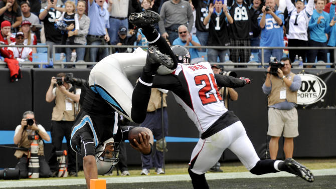 FILE - In this Dec. 9, 2012, file photo, Carolina Panthers quarterback Cam Newton (1) dives into the end zone for a touchdown as Atlanta Falcons' Chris Owens (21) pursues during the second half of an NFL football game in Charlotte, N.C.  The Panthers second-year quarterback had his best game of the season, but the highlight occurred as he was crossing the goal line to complete a 72-yard scoring run. He somersaulted into the end zone, and as his legs were in the air, he was nudged slightly by a Falcons defensive back. (AP Photo/Rainier Ehrhardt, File)
