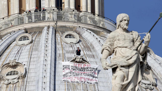 "Firefighters look at Italian businessman Marcello di Finizio standing above his banner  which reads in Italian ""Help!! Enough Monti (Italian Premier Mario Monti), enough Europe, enough multinationals, you are killing all of us. Development?? This is a social butchery!!"", as he protests on St. Peter's 130-meter-high (42-feet-high) dome, at the Vatican, Wednesday, Oct. 3, 2012. An Italian man has eluded Vatican security and scaled the 130-meter-high (42-feet-high) dome of St. Peter's Basilica to protest Italian government and European Union policies. Officials said Wednesday that the man, who identified himself as the owner of a beach resort, refused appeals from government ministers offering to meet with him if he would come down. (AP Photo/Andrew Medichini)"