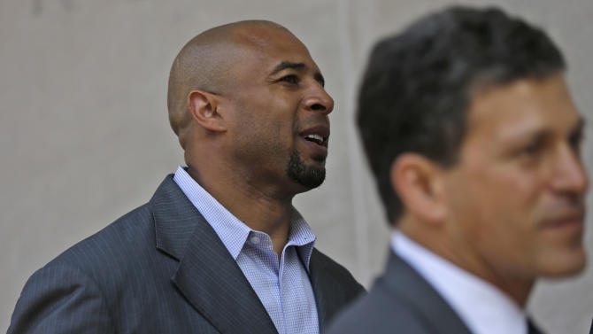 Former NFL player Dorsey Levens, left,  walks to the U.S. Courthouse Tuesday, April 9, 2013, in Philadelphia for a hearing to determine whether the NFL faces years of litigation over concussion-related brain injuries. Thousands of former players have accused league officials of concealing what they knew about the risk of playing after a concussion. The lawsuits allege the league glorified violence as the game became a $9 billion-a-year industry.  (AP Photo/Matt Rourke)