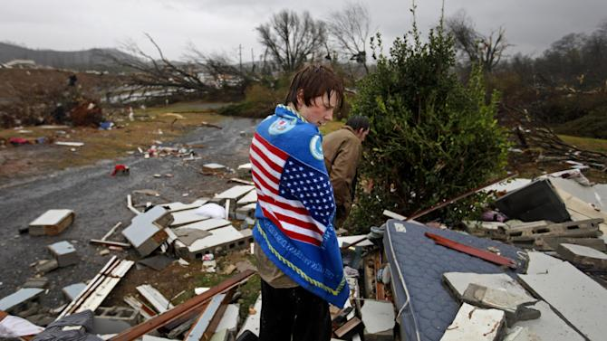 Will Carter, 15, wraps himself up in a towel he found while searching debris for the family dog, a pit bull named Niko, upon arriving to his damaged home from school following a tornado, Wednesday, Jan. 30, 2013, in Adairsville, Ga. A fierce storm system that roared across Georgia has left at least one person dead after it demolished buildings and flipped vehicles on Interstate 75 northwest of Atlanta. (AP Photo/David Goldman)