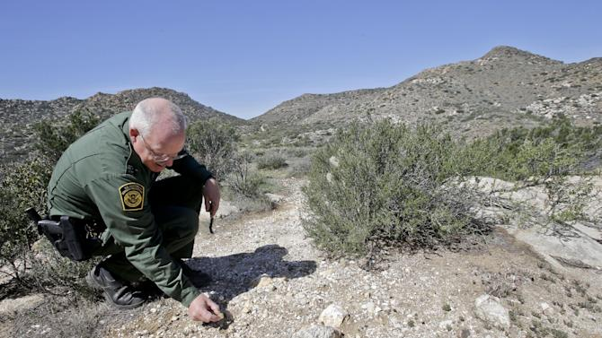 """In this Monday, March 25, 2013 photo, Border Patrol agent Richard Gordon, a 23-year veteran of the agency, examines color changes in the soil which tell him volumes about human traffic where illegal immigrants enter the United States in the Boulevard area east of San Diego  in Boulevard, Calif. For the past 16 years, Gordon has been one of the top """"sign-cutters"""" or trackers in the Border Patrol. (AP Photo/Lenny Ignelzi)"""