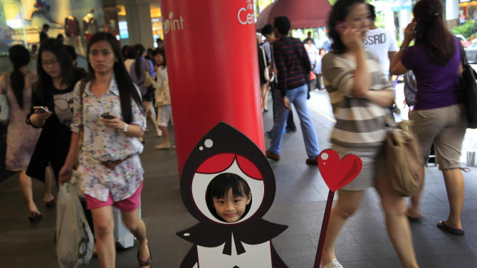 FILE - In this March 12, 2012 file photo, a young girl poses as the Jack of Spades while shoppers make their way past her on a busy shopping street, in Singapore. Already one of the most densely populated countries in the world, tiny land scarce Singapore is projecting its population to swell by a third over the next two decades. To accommodate the influx, its planners envisage expanding upward, outward and downward. The population target of 6.9 million people, an increase of 1.3 million from the present, is contentious in a country where rapid immigration has already strained services such as public transport and contributed to a widening wealth gap. (AP Photo/Wong Maye-E, File)