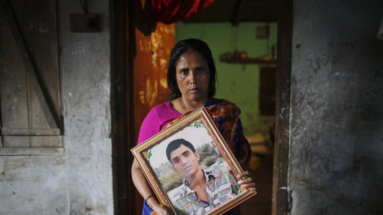 Fatema holds a picture of her son Nurul Karim as she poses for a photograph in front of her slum house in Savar