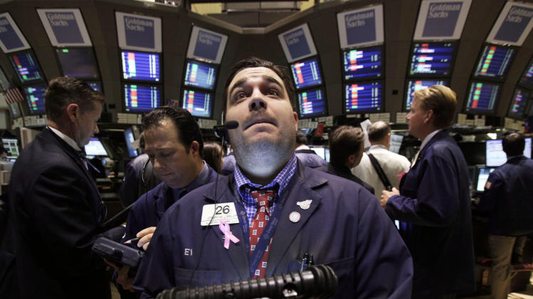 Trader Joseph Lawler, center, works on the floor of the New York Stock Exchange Tuesday, Oct. 9, 2012. Another dire prediction about global economic growth is sending stocks lower on Wall Street in early trading on Tuesday. (AP Photo/Richard Drew)