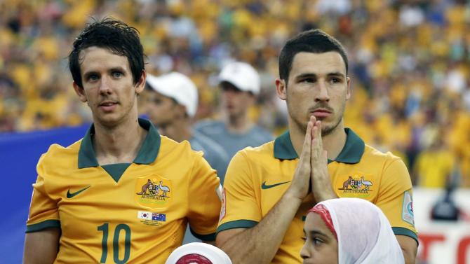 Australia's Robbie Kruse and Mathew Leckie react as the teams line up before the Asian Cup final soccer match between South Korea and Australia at the Stadium Australia in Sydney