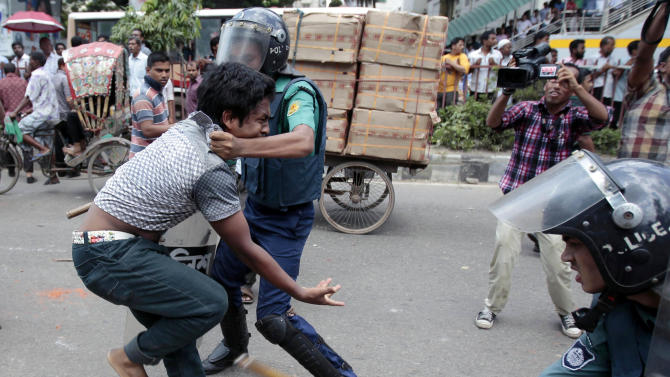 Bangladeshi policemen detain an activist of an Islamic group during a protest in Dhaka, Bangladesh, Saturday, Sept. 22, 2012. Officials and witnesses said scores of people were injured in a clash in Bangladesh's capital between police and hundreds of Muslims who were protesting a film produced in the United States that denigrates the Prophet Muhammad. (AP Photo/A.M. Ahad)