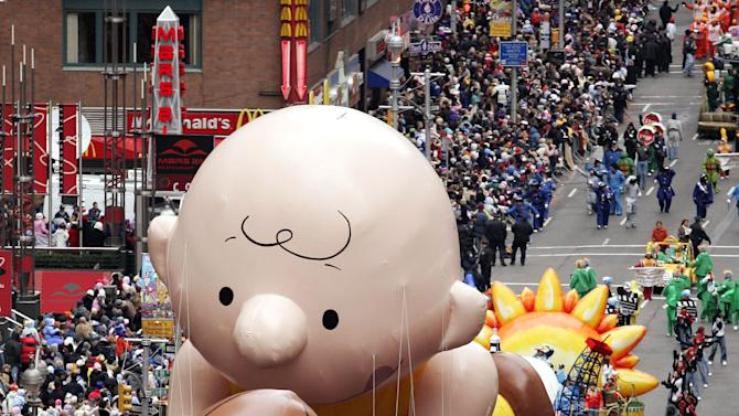FILE - This Nov. 24, 2005 file photo shows a balloon of Peanuts character Charlie Brown chasing a football down Broadway during the Macy's Thanksgiving Day parade in New York.  The parade has to be a crowd-pleaser for a multigenerational crowd. More than 3 million people typically attend the event that also unfolds in front of a TV audience of 50 million. This year's parade will feature balloons include Papa Smurf and the Elf on a Shelf, while Buzz Lightyear, Sailor Mickey Mouse and the Pillsbury Doughboy keep their place in the lineup. A new version of Hello Kitty is also to be included. (AP Photo/Jeff Christensen, file)