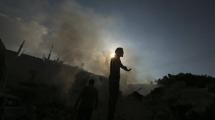 A Palestinian standing atop the remains of a house reacts as smoke rises in Gaza City