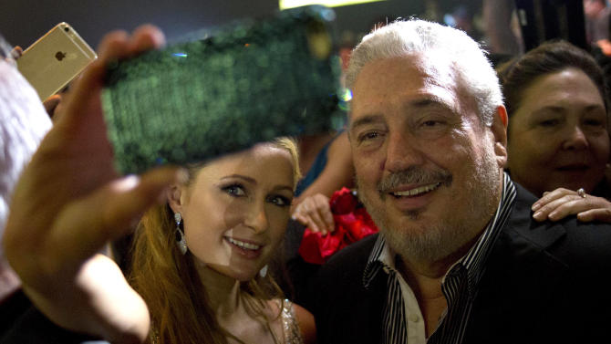 Celebrity Paris Hilton, left, takes a selfie with Fidel Castro Diaz-Balart, son of Cuba's leader Fidel Castro during the gala dinner of the 17th Cigar Festival in Havana, Cuba, Friday, Feb. 27, 2015. (AP Photo/Ramon Espinosa)
