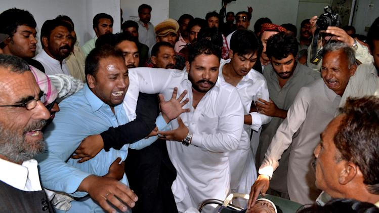 "Pakistani men mourn over the lifeless body, bottom right, of a provincial lawmaker Handery Masieh at a local hospital in Quetta, Pakistan, Saturday, June 14, 2014. A guard for a provincial Christian lawmaker shot and killed the legislator during a meeting Saturday in southwest Pakistan, police said. Government spokesman Jan Mohammad Buledi said the guard fled after the attack and police were trying to arrest him. ""We do not know why the guard killed Handery Masieh, and everything will be clear when we arrest him,"" he told reporters. (AP Photo/Arshad Butt)"