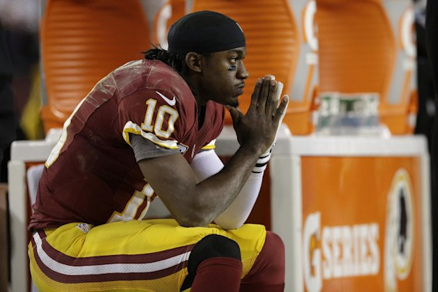 Washington Redskins quarterback Robert Griffin III sits on the bench after a knee injury during an NFL wild card playoff football game against the Seattle Seahawks in Landover, Md., Sunday, Jan. 6, 20