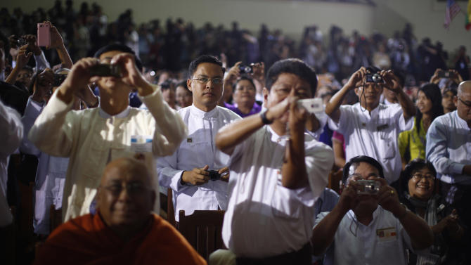 Members of the audience take pictures as U.S. President Obama delivers remarks at University of Yangon