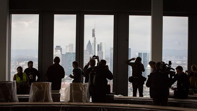 Journalists stand in front of a window in an almost-finished conference room on the 41st floor of the new headquarters of the European Central Bank (ECB) in Frankfurt Germany  Tuesday Oct. 21, 2014. In background the skyline of Frankfurt.  (AP Photo/dpa,Frank Rumpenhorst)