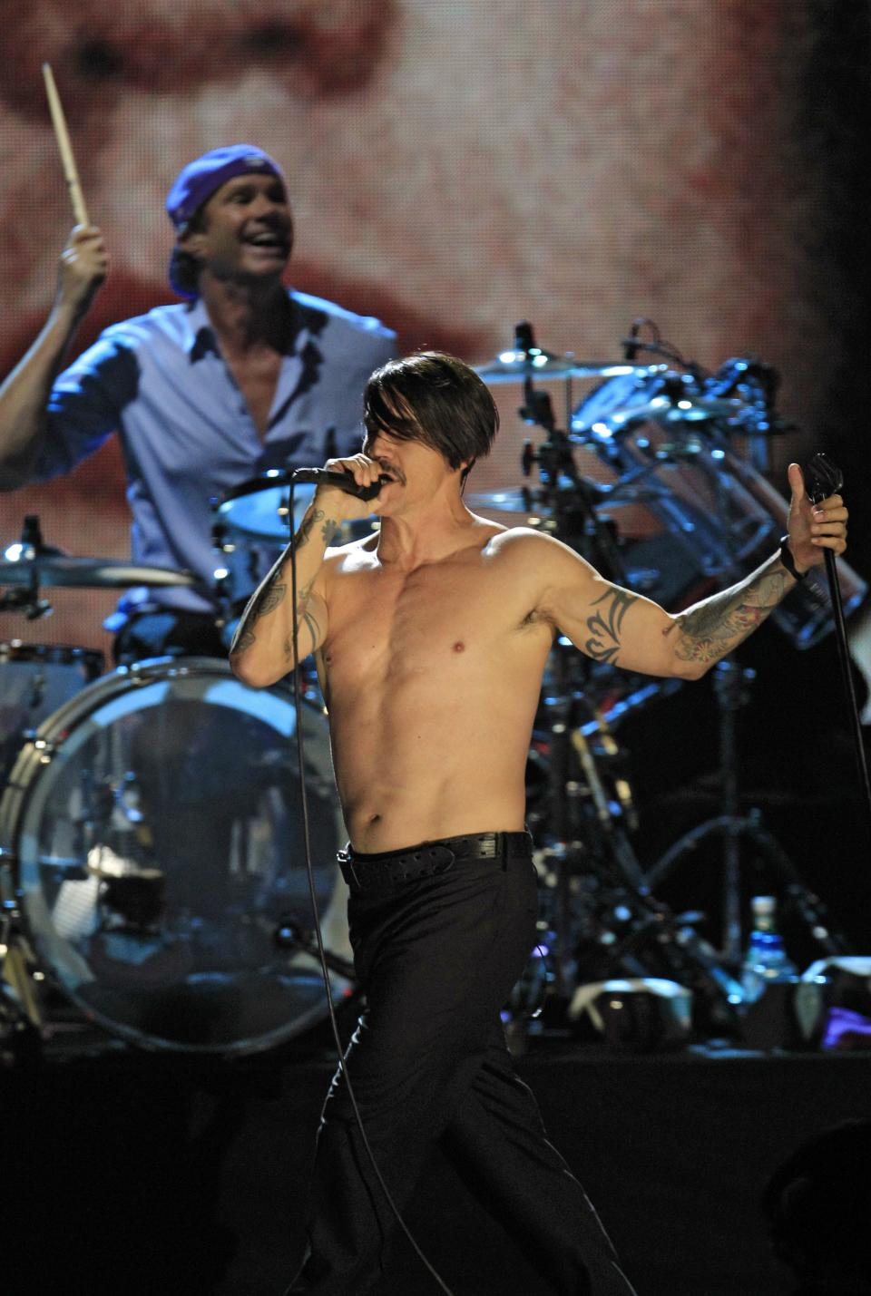 Red Hot Chili Peppers' Anthony Kiedis performs with drummer Chad Smith, background after induction into the Rock and Roll Hall of Fame Sunday, April 15, 2012, in Cleveland. (AP Photo/Tony Dejak)
