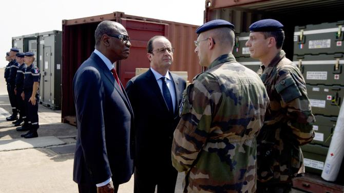 French President Hollande and Guinea's President Alpha Omar Conde speak with French soldiers in charge of humanitarian supplies at Conakry Airport