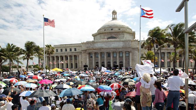 "In this Feb. 18, 2013 photo, demonstrators stand outside the capitol building during a ""Puerto Rico Rises"" rally to protest any move to legalize same-sex marriage in San Juan, Puerto Rico. The governing Popular Democratic Party is pushing a bill through the legislature that would outlaw discrimination based on gender or sexual orientation, a step taken by about half of U.S. states. Another bill would extend a domestic violence law to gay couples. However, many Puerto Ricans remain uncomfortable with the changes. Church groups in February rallied an estimated 200,000 people against a move to include gay couples under domestic violence laws. (AP Photo/El Vocero, Sebastian Marquez Velez)"