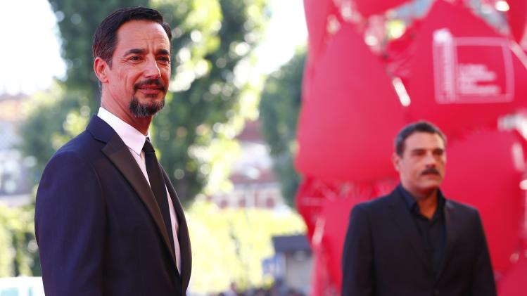 """Actors Mazzotta and Leonardi pose during the red carpet for the movie """"Anime Nere"""" (Black Souls) at the 71st Venice Film Festival"""