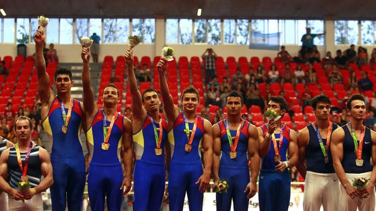 Colombia's gymnastics team pose for the media, after winning Gold medals, during the podium awards ceremony of the gymnastics team competition category at the South American Games in Santiago