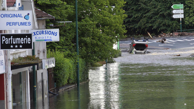 A street is flooded in Lourdes southwestern France, Wednesday, June 19, 2013. French rescue services and police are evacuating hundreds of pilgrims from hotels threatened by floodwaters from a rain-swollen river in the Roman Catholic shrine town of Lourdes. (AP Photo/Bob Edme)