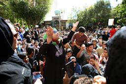 Iranians take part in a protest in front …