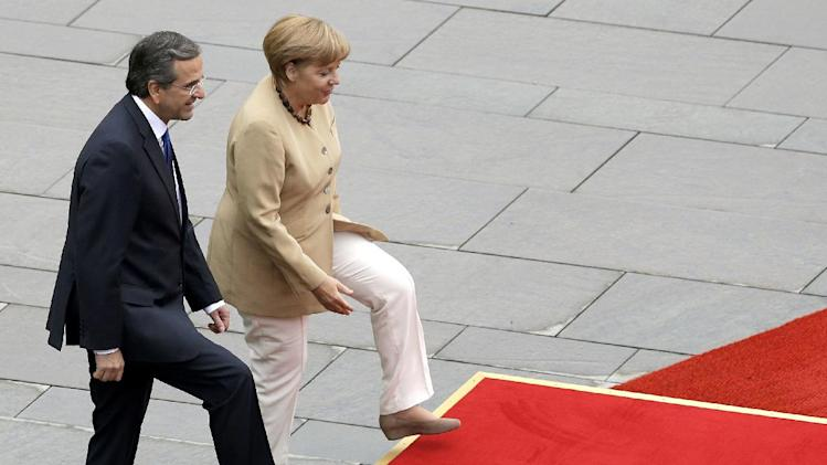 German Chancellor Angela Merkel, right, and the Prime Minister of Greece Antonis Samaras,  step on a podium to listen to the national anthems during a welcome ceremony prior to a meeting at the chancellery in Berlin, Germany, Friday, Aug. 24, 2012. (AP Photo/Michael Sohn)