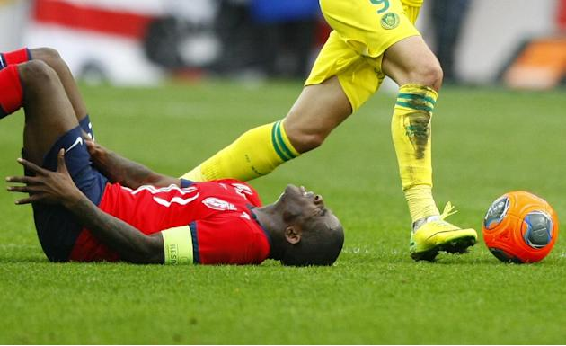 Lille's Antonio Mavuba grimaces after a crash during his French League one soccer match against Lille at the Lille Metropole stadium, in Villeneuve d'Ascq, northern France, Saturday, March. 15