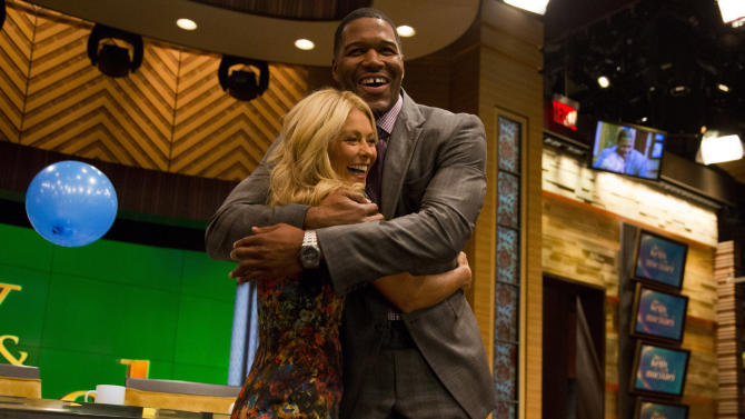 """Former football player Michael Strahan, right, embraces Kelly Ripa on the set of the newly named """"Live! with Kelly and Michael"""" on Tuesday, Sept. 4, 2012 in New York. Strahan joined the popular morning show as a permanent co-host on Tuesday, fulfilling a joking prophecy he made to Regis Philbin more than four years ago. The gap-toothed former New York Giant jogged onto the morning show set and picked up co-host Kelly Ripa in a bear hug, lifting her off her feet. He replaces Philbin, who left last November. Strahan was the survivor in a series of on-air tryouts of potential co-hosts since Philbin left, and his hiring has been an open secret for the past two weeks. (Photo by Charles Sykes/Invision/AP Images)"""