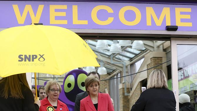 First Minister for Scotland Nicola Sturgeon (C) leaves a theme park in Motherwell after a campaign visit in central Scotland