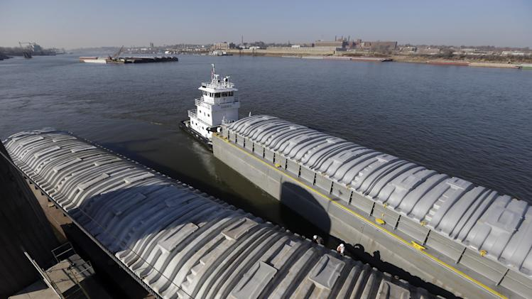 FILE - In this Nov. 28, 2012 file photo, a tow switching barges pulls an empty barge along side one filled with soybeans at an Archer Daniels Midland grain river terminal along the Mississippi River in Sauget, Ill. From Montana to West Virginia, officials from across the country have written to President Barack Obama urging him to intervene _ or not _ in a dispute about whether water from the Missouri River's upstream reservoirs should be released to flow into the Mississippi River, where low water levels have imperiled commercial traffic along a 180-mile stretch between St. Louis and Cairo, Ill.  (AP Photo/Jeff Roberson, File)