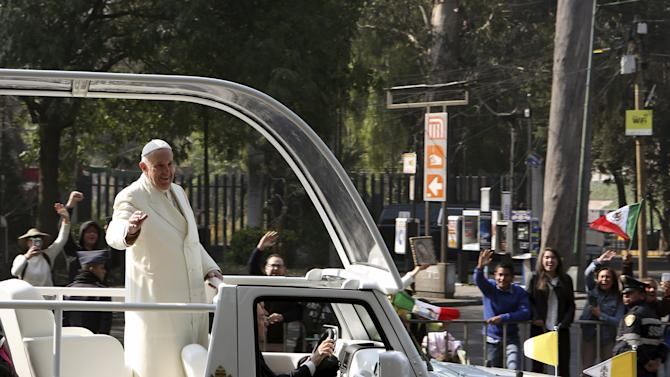 Pope Francis waves to the crowd in Mexico City before boarding a helicopter to fly to Ecatepec