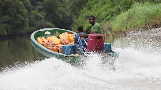 In this photo taken Saturday, May 18, 2013, an Unidentified man ride a speed boat with oil containers at the creeks of Bayelsa, Nigeria. The first drops of crude float in the languid muddy currents of Nigeria's oil-rich southern delta, then slowly grow into the splatter of massive crime scene. Oil thefts, long a problem in the Niger Delta, are growing at an ever-faster rate despite government officials and international companies offering increasingly dire warnings about the effect on Nigeria's crude production. Some 200,000 barrels a day representing about 10 percent of Nigeria's production are siphoned off pipelines crisscrossing the region. (AP Photo/Sunday Alamba)