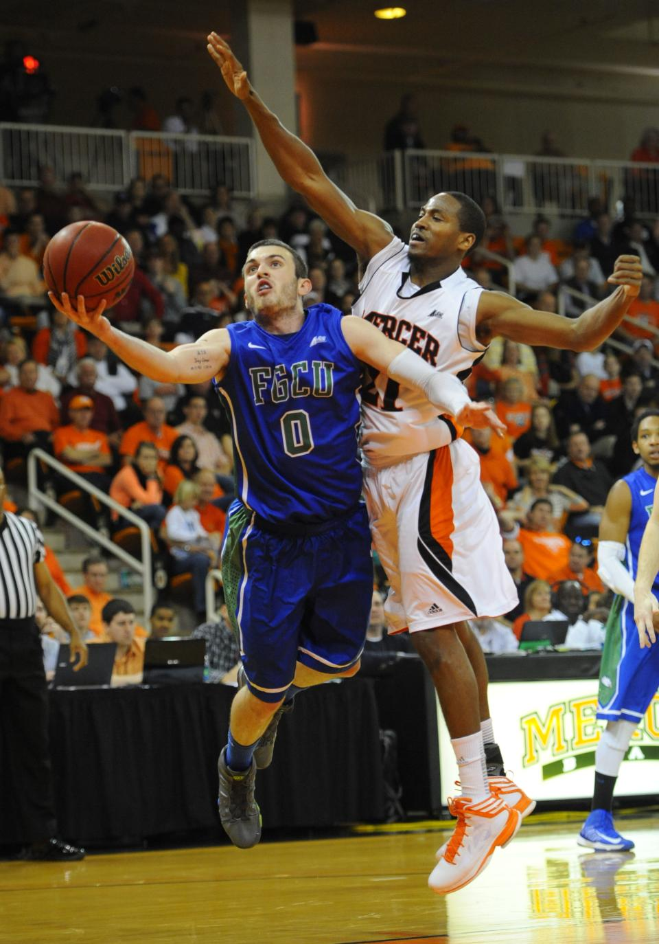 Florida Gulf Coast's Brett Comer (0) works against Mercer's Langston Hall (21) during the first half of the Atlantic Sun championship game in Macon, Ga., Saturday, March 9, 2013.  (AP Photo/Woody Marshall)