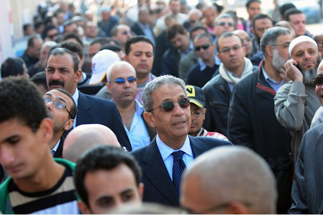 FILE - In this Nov. 28, 2011 file photo, Egyptian presidential hopeful Amr Moussa, center, waits outside a polling station before voting on the first day of parliamentary elections in Cairo, Egypt. In