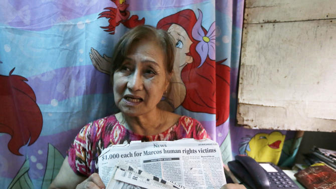 In this Jan. 26, 2013 photo, Carmencita Florentino, 64, holds newspaper clippings during an interview in her home at a poor neighborhood of Tatalon, Quezon city, northeast of Manila, Philippines. Florentino was jailed twice, in 1977 and 1978, during the Martial Law period imposed by the late Philippine strongman Ferdinand Marcos. More than 9,000 victims will be awarded compensation using $246 million that the Philippine government recovered from Marcos' ill-gotten wealth. But all claims will still have to evaluated by an independent commission and the amount each will receive will depend of the abuse suffered. (AP Photo/Bullit Marquez)