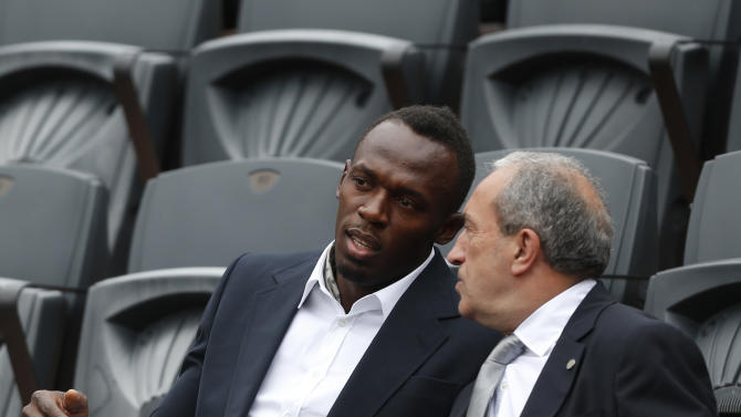 Jamaica's Usain Bolt, left, talks with Jean Gachassin, head of the French Tennis Federation, before the men's final opposing Spain's Rafael Nadal to compatriot David Ferrer during the men's final match of the French Open tennis tournament at the Roland Garros stadium Sunday, June 9, 2013 in Paris. (AP Photo/Petr David Josek)