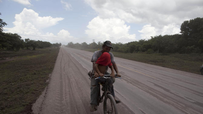 A young man covers his face with his T-shirt while riding a bicycle on a road covered with volcanic ash spewed from the San Cristobal volcano, near Chinandega, Nicaragua, Saturday, Sept. 8, 2012. Nicaragua's tallest volcano, located about 70 miles (110 kilometers) northwest of Managua, near the Honduran border, has let off a series of explosions, spewing gases and showering ash on nearby towns, prompting an evacuations of residents. (AP Photo/Esteban Felix)