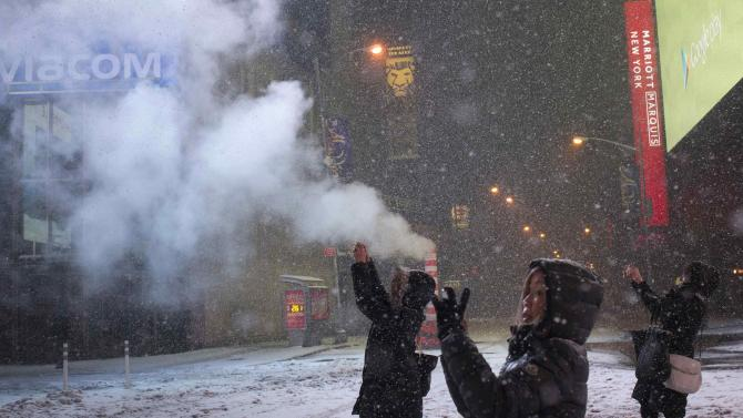Female tourists use their smart phones to capture a snow storm in Times Square, New York