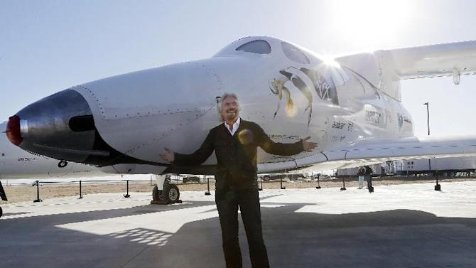 "FILE - In this Sept. 25, 2013, file photo, British entrepreneur Richard Branson poses with SpaceShipTwo at a Virgin Galactic hangar at Mojave Air and Space Port in Mojave, Calif. The Virgin Galactic's SpaceShipTwo space tourism rocket exploded Friday, Oct. 31, 2014, during a test flight, killing a pilot aboard and seriously injuring another while scattering wreckage in Southern California's Mojave Desert, witnesses and officials said. Virgin Galactic would not say what happened other than that it was working with authorities to determine the cause of the ""accident."" (AP Photo/Reed Saxon, File)"